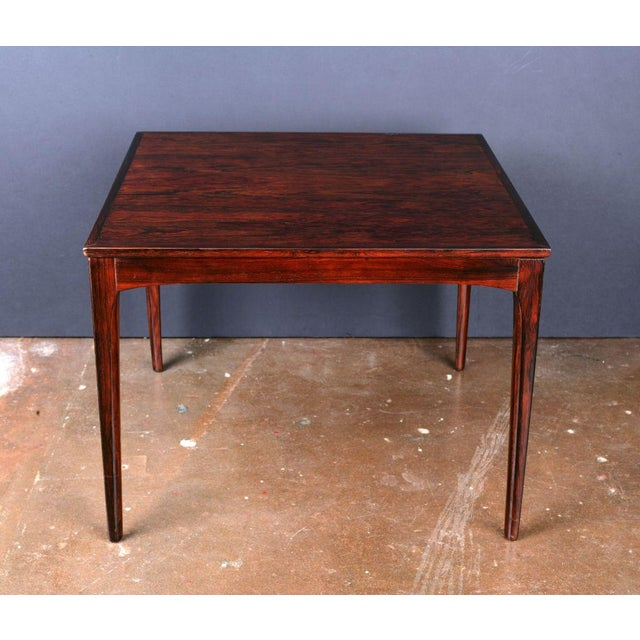 An elegant Art Deco period square table with slight, tapering legs. Beautiful and rich Amboyna veneer, finished with a...