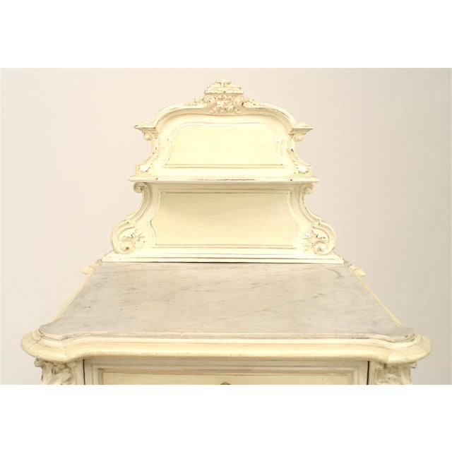 French Victorian white painted and carved bedside commode with inset marble top and a shaped backrail.