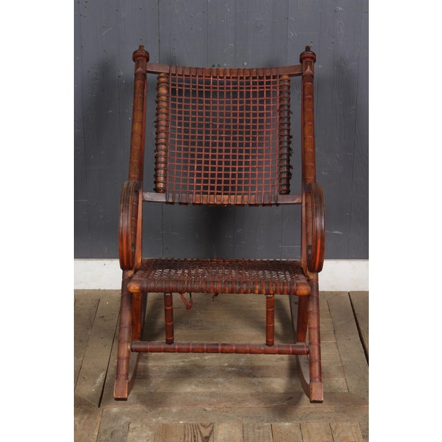 Ornately carved rocking chair in rich brown wood. Wood frame with fabric-wrapped woven metal seat and back. Some wear to...