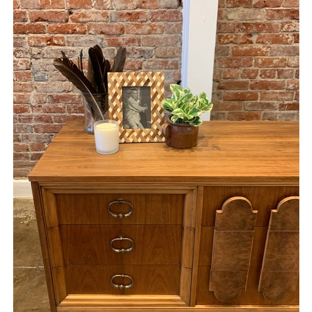 Mid century burlwood dresser/credenza with unique front panel and brass accents. 9-drawers make for wonderful storage and...