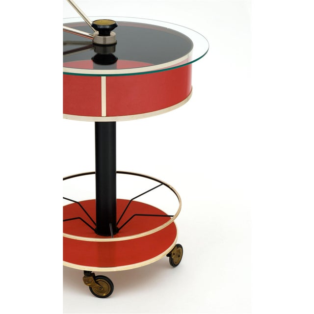 Bar cart from Italy made of lacquered tole and brass and featuring a hydraulic system sealing the drum shaped shelf with a...
