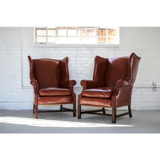 Pure Class. Classic style in this pair of deep red marbled leather Georgian H-base Wing-back Fireside Chairs. Solid...