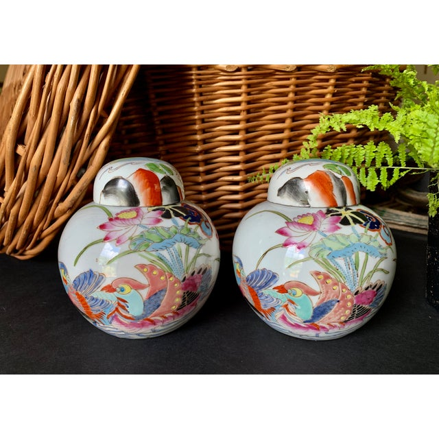 Vintage pair of Chinoiserie lidded porcelain jars / vases with a colorful hand-painted wood duck & water lily design....