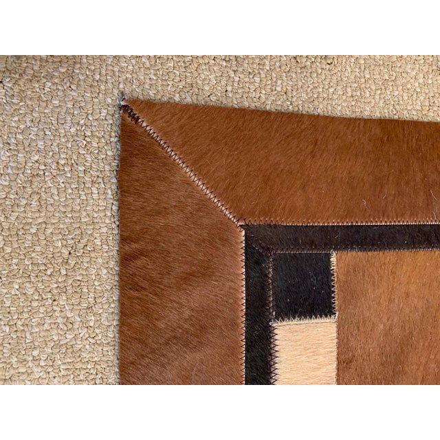 A great looking cowhide area rug in brown, cream and black that has a woven or patchwork geometric design.