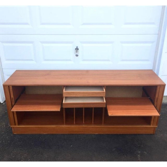 This stylish tambour cabinet features danish teak veneer with spacious interior shelf space and dovetailed pull out...