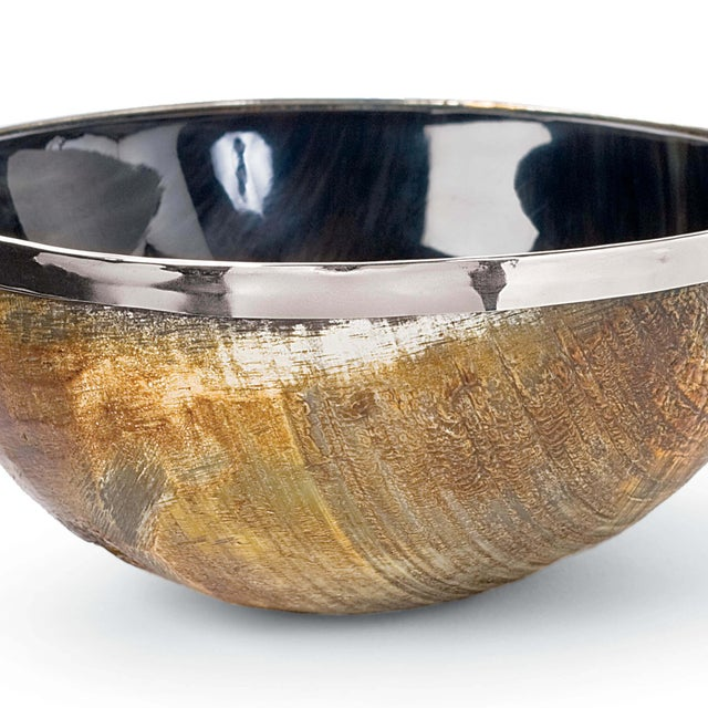 Polished natural horn and a metallic brass trim form the exterior of this bowl; a dark polished interior serves as a...