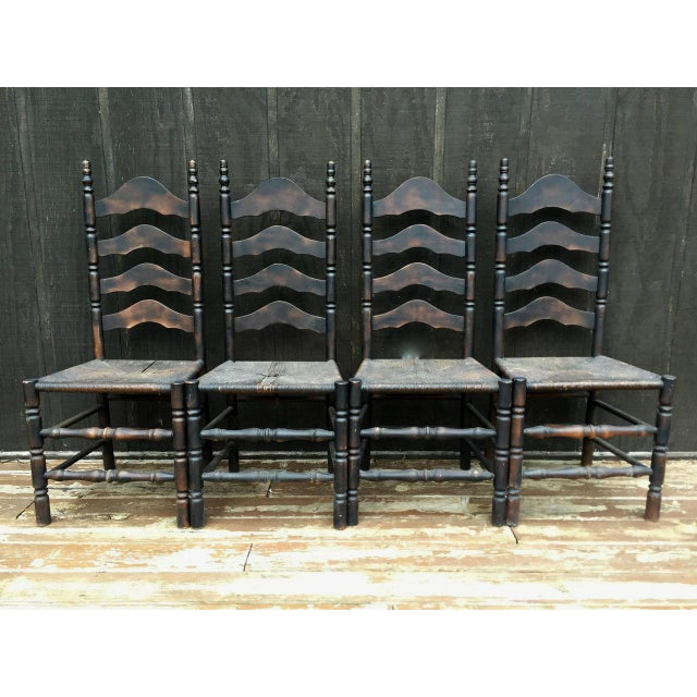 Set of four French farmhouse ladderback rush seat chairs. We love the dark stain on this set of farmhouse rustic dining...