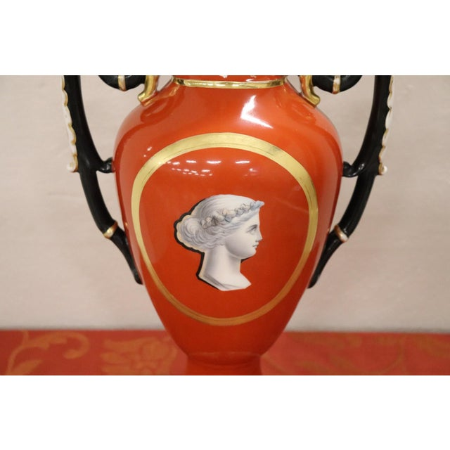 Beautiful ceramic vase in the shape of an amphora painted in shades of red with central portrait. Beautiful handles in...