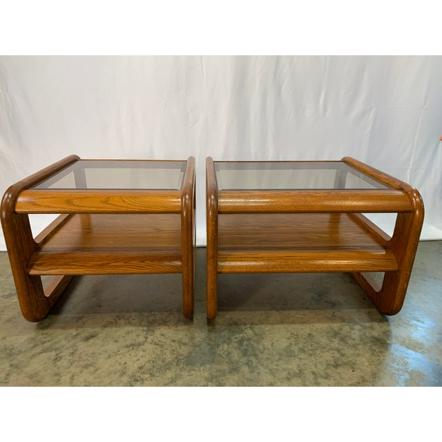 A set of two California design Mid-Century Modern Lou Hodges oak end tables. Each table has an inset smoked grey glass top...