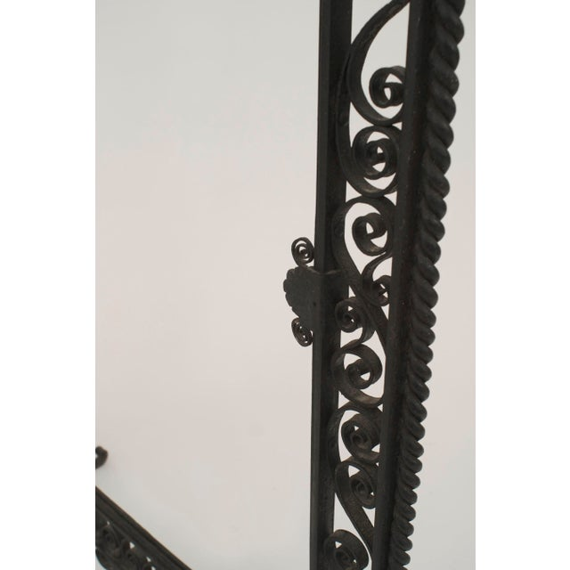 American Art Deco wrought iron fire screen with a filigree and scroll design border and raised on scroll feet