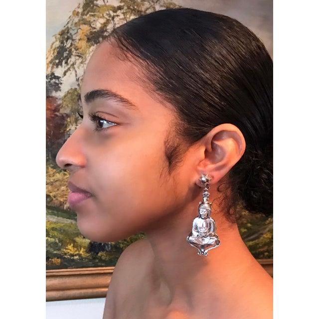 Circa 1940/50s light-weight, ornately detailed, silver tone metal Buddha earrings. Each dangling, screw-back earring...