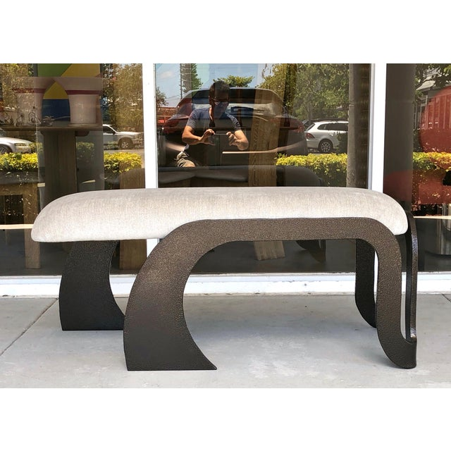 A pair of abstract benches. The frames are heavy steel with a thick glass like enamel finish in what resembles hammered...