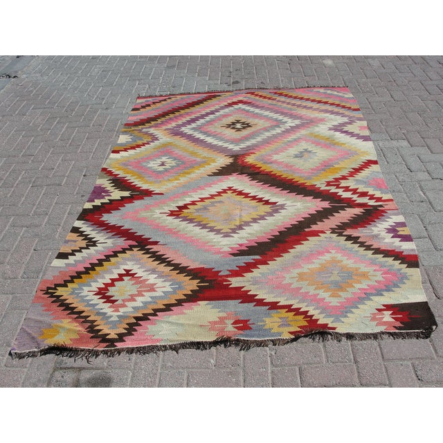 Offered is a vintage handwoven Turkish kilim rug. The kilim is nearly 65 years old. It is handmade of very fine quality...