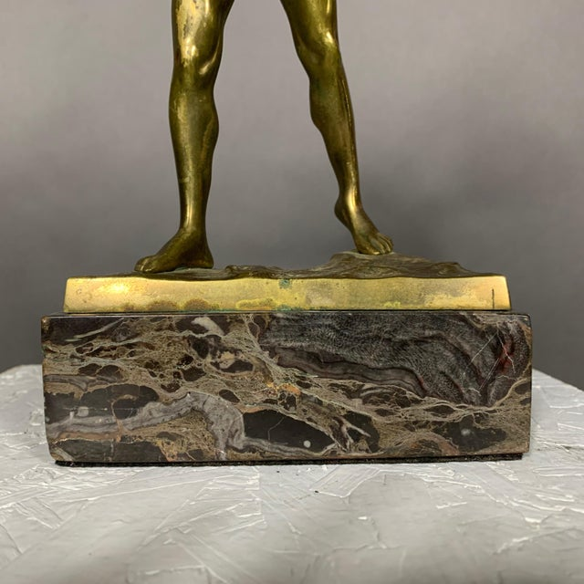 A gold tinted bronze sculpture on marble base of a semi-nude gladiator with shield and spear. Signed on bronze base. Some...