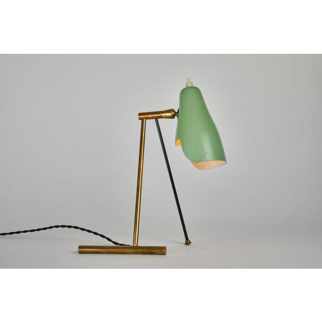1950s Stilnovo wall or table lamp. Featuring two sculptural brass and painted metal legs, with the original green...