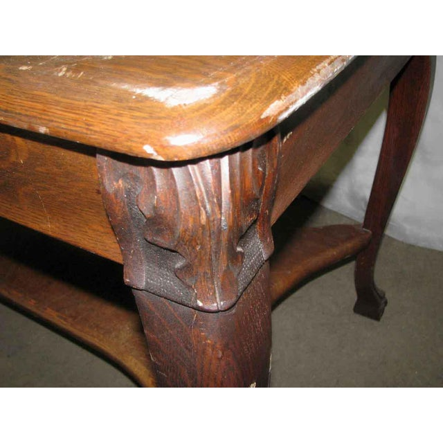 Turn of the century solid oak table or desk with drawer. The corners are detailed with leafy carvings and finished with...