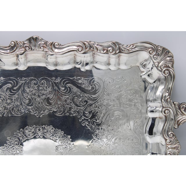 Lovely, antique silver plated tray from France, crafted circa 1920. This elegant serving tray sits on four detailed feet...