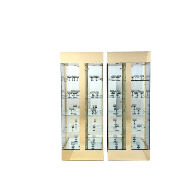 Amazing pair of Mid Century Modern lighted brass and glass and mirror display cabinets. Each glass shelf has a plate...