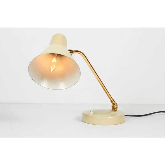 An Italian 1950s ivory enamel and brass articulated desk table lamp.