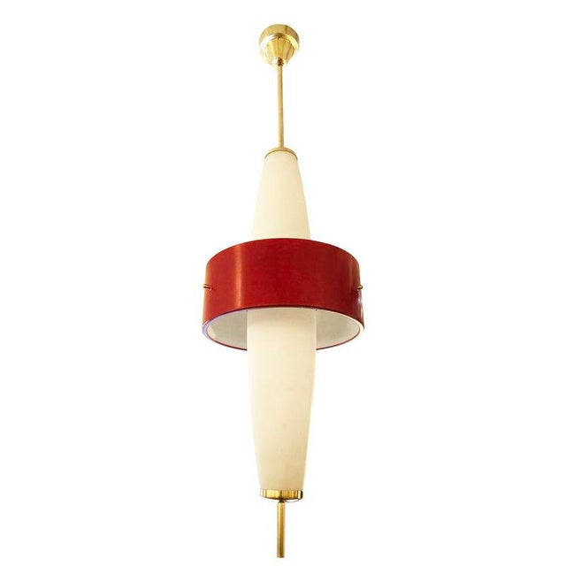Stilnovo pendant with two elongated frosted glass shades and a central red aluminum ring. Brass hardware and fittings....