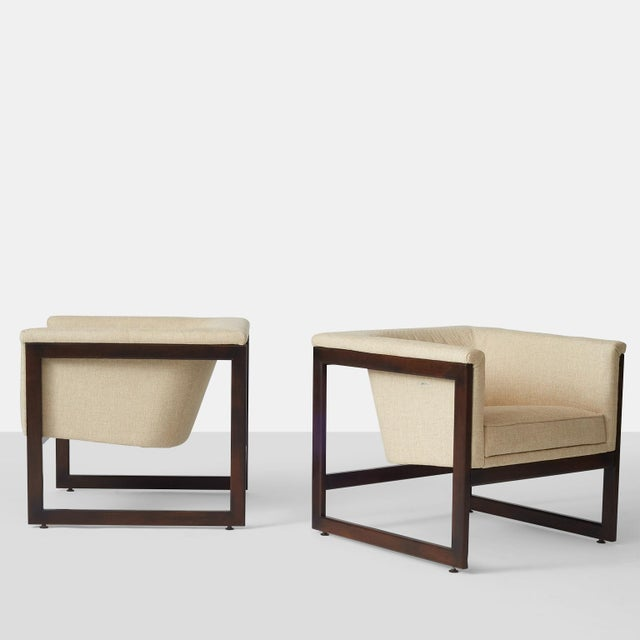 A pair of Milo Baughman floating cube lounge chairs with wooden frame and upholstered seat in a ivory woven fabric....