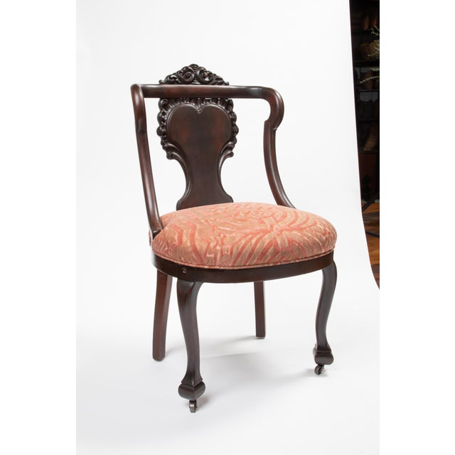 Pair of carved mahogany wooden chairs with front casters in brass, upholstered in Fortuny's Altare fior di pesco & copper...