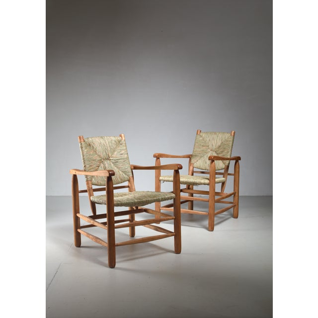 A pair of Charlotte Perriand chairs made of an oak frame with a woven rush seat and back rest. This model no. 21 chair was...