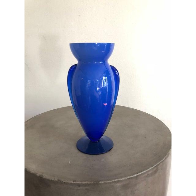 Vintage glass vase with winged side details in a brilliant blue hue.