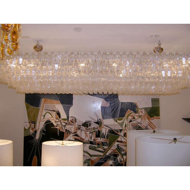 A large rectangular chandelier with tiered polyhedral clear glass on a white painted metal frame by Venini, Italian C....