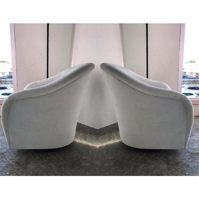 Gorgeous pair of Mid-Century Modern lounge chairs with swivel base design. Chairs have barrel back form with elegant...