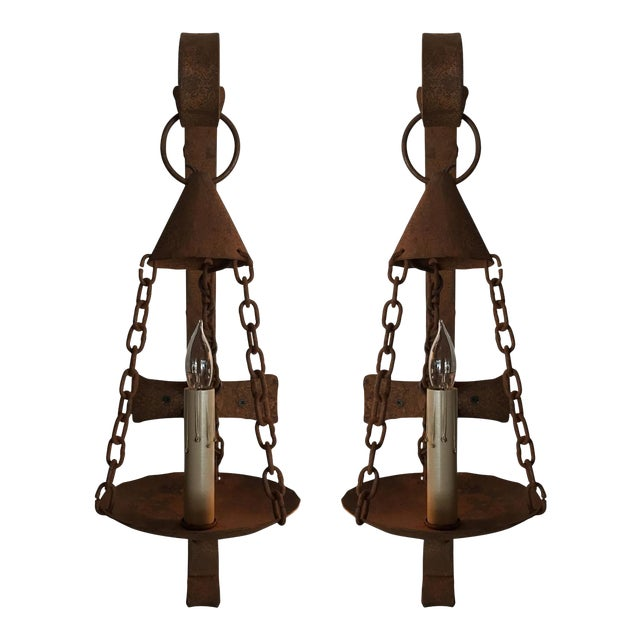 Diminutive country style iron sconce. Sold individually. This listing is for a single unit but 14 are available.