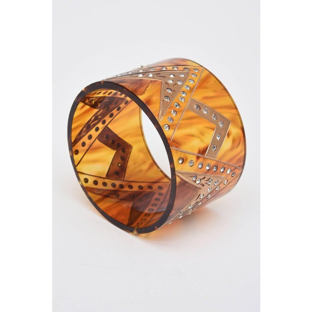 This French wide cuff bracelet has inverted V's with gold applied and rhinestones adorning the v patterns.. It is amber...