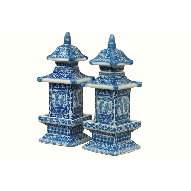 A pair of Chinoiserie blue and white ceramic pagoda shaped jars. The top tier lifts off to reveal a storage area. Each...