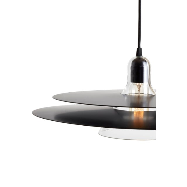 Cymbal is a pendant lamp made of blown glass and two slightly convex trays. The chrome version looks transparent as it...