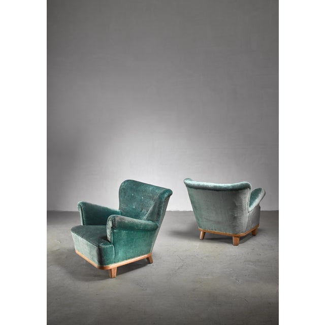 A pair of comfortable Swedish easy chairs with scrolled armrests. The chairs stand on an oak and pine frame and have a...