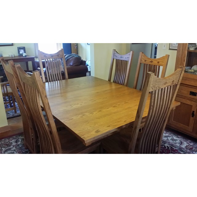 "Amish made solid quarter-sawn oak dining table with 8 chairs. 2 armchairs and 6 side chairs. Comes with 2 - 12"" leaves...."