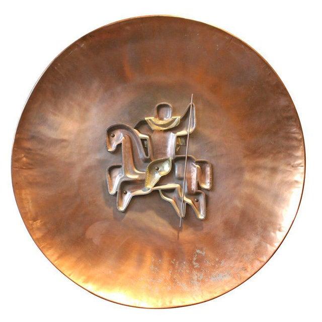 Riveted copper horseback rider on round copper disc.