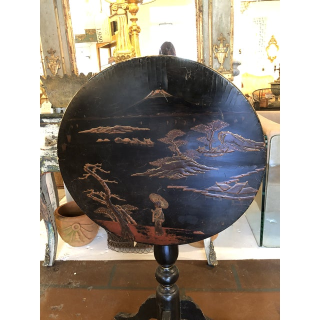 Painted black lacquer chinoiserie tilt top side table. This round top table sits on a pedestal base with three cabriole...