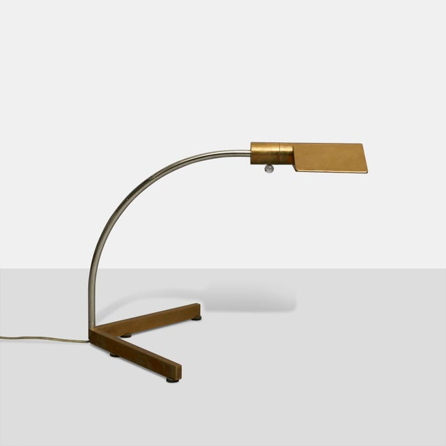 """An arced desk lamp in chrome and brass with lucite dimmer switch. Stamped to the base """"Cedric Hartman."""""""