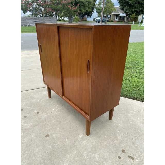 Super fine teak Nils Jonsson sliding door cabinet with shelves. Near perfect condition. The slightest little chip at the...