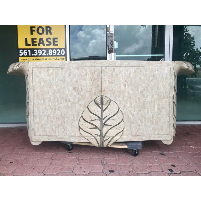 Beautiful tessellated stone credenza with inlaid brass by Maitland Smith. Has Verotoimisto detailed leaf motive. In...