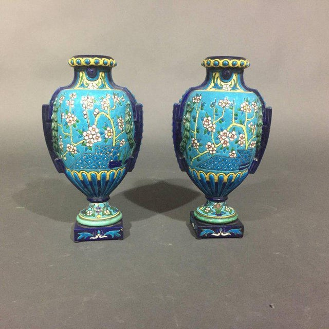 """This pair of enameled ceramic 11 1/2"""" faience vases are in perfect Emaux de Longwy cloisonné form with petite white floral..."""
