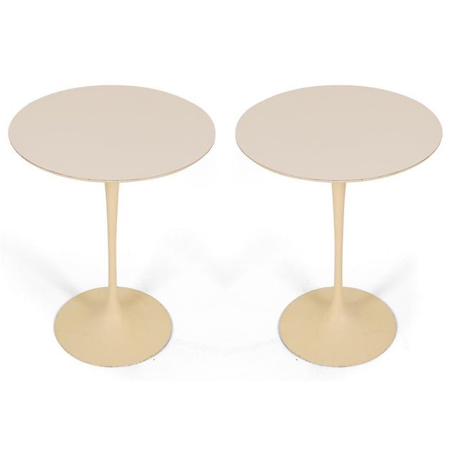 A vintage pair of classic Mid Century Modern round 'tulip' side tables with white laminate tops supported on enameled cast...