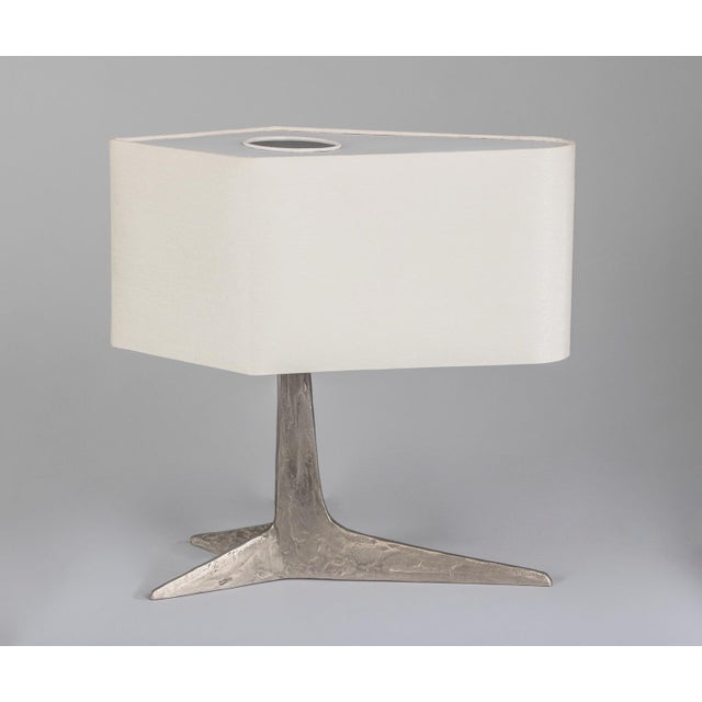 A rare sculptural brutalist table lamp by Felix Agostini, in nickeled bronze with a tripartite abstracted clawfoot base...