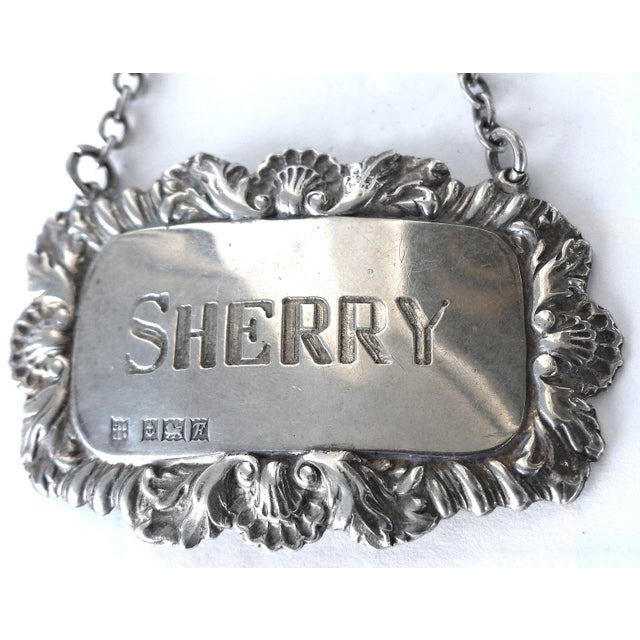 Offered is an ornate sterling silver Sherry decanter or bottle tag/label with a chain for hanging. -The tag is marked...
