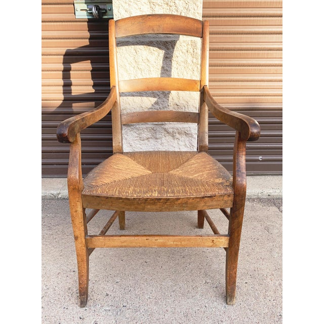 Antique walnut rush armchair from France, c 1860. Lovely patina and charming scroll on arms and back rail. Rush seat is...