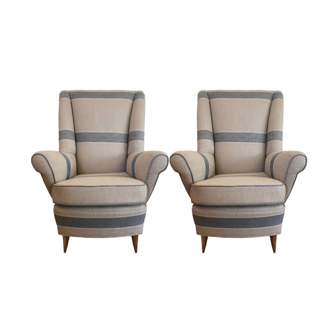 Striped newly upholstered Mid-Century Modern 1940's armchairs with out-curved armrests, tall backrests and medium stained,...