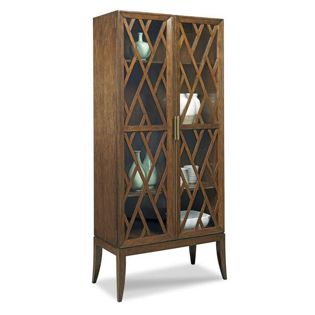 A striking Display Cabinet featuring a pierced fretwork overlaid on a glass doors with refined brass pulls. Material:...