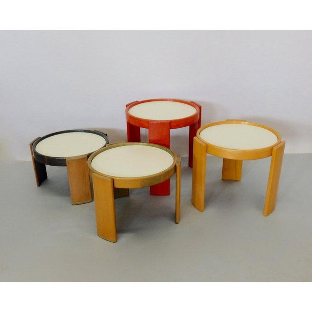 Four round graduated height occasional tables. Tops are reversable to show white or black. Early Cassina labels are intact...