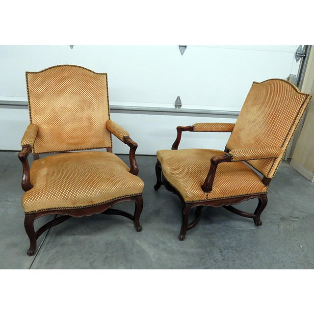 Pair of Country French armchairs with textured upholstery and nail head trim.